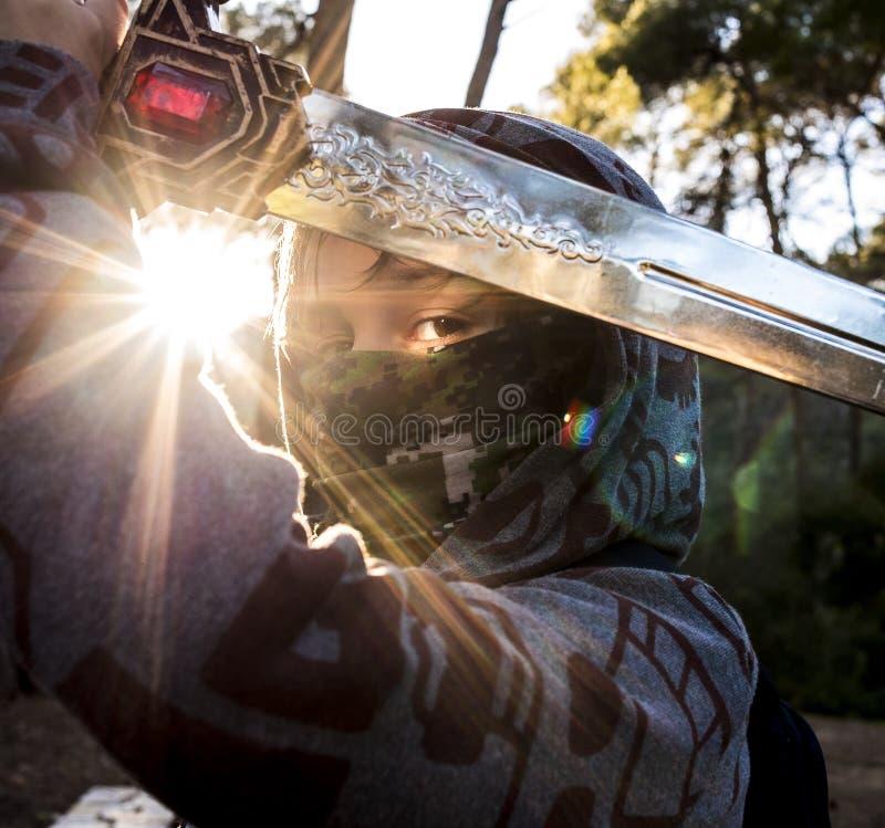 Luta do menino do guerreiro na montanha no por do sol foto de stock royalty free