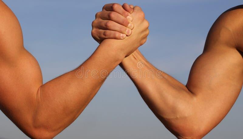 Luta romana de braços, competição, comparação da força CONTRA Povos, lazer, desafio Conceito da rivalidade - fim acima de masculi imagem de stock