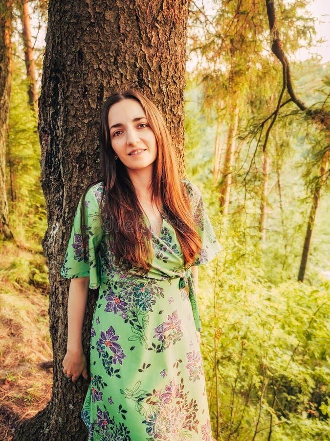 Lutade den härliga le caucasian brunettflickan för ståenden med långt hår i skogen på solnedgången tillbaka mot ett träd royaltyfria foton