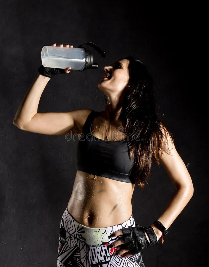 Lutador fêmea desportivo do pugilista ou do Muttahida Majlis-E-Amal que bebe e que espirra a água em sua cara mulher fêmea bonita foto de stock royalty free