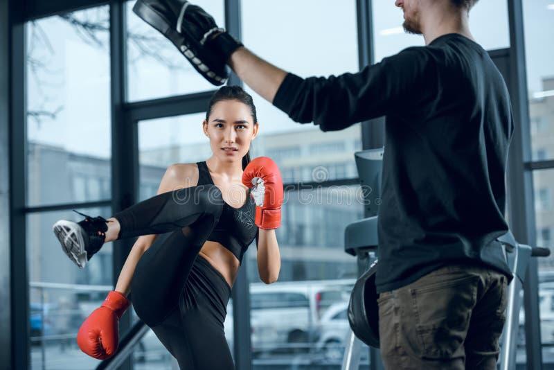 lutador fêmea novo que executa o baixo pontapé com o instrutor foto de stock