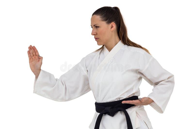 Lutador fêmea que executa a posição do karaté fotografia de stock
