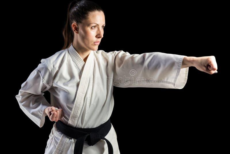 Lutador fêmea que executa a posição do karaté foto de stock royalty free