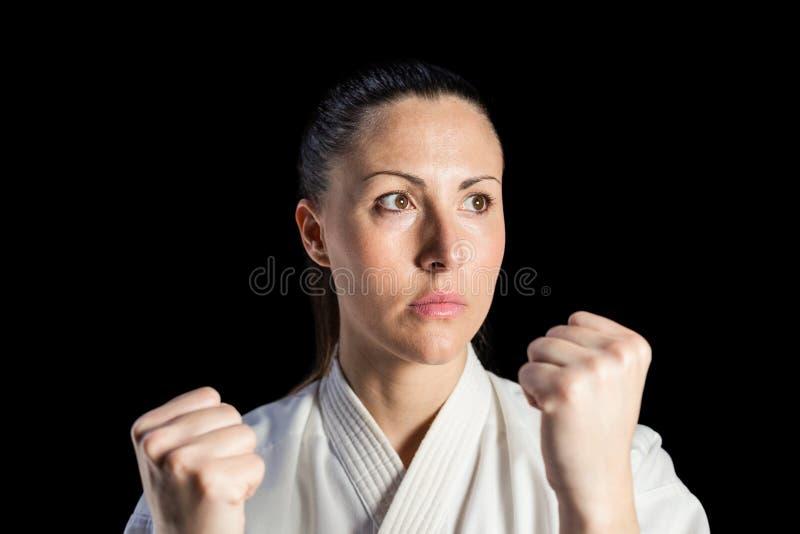 Lutador fêmea que executa a posição do karaté imagem de stock royalty free