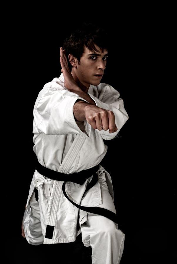 Lutador masculino novo do karaté do contraste elevado no preto fotos de stock