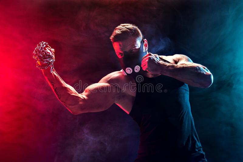 Lutador muscular sério que faz o perfurador com as correntes trançadas sobre seu punho fotos de stock