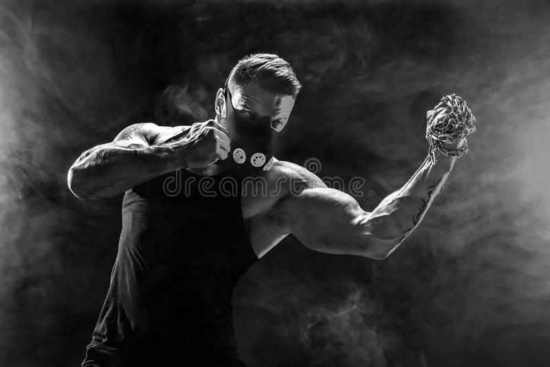 Lutador muscular sério que faz o perfurador com as correntes trançadas sobre seu punho foto de stock royalty free