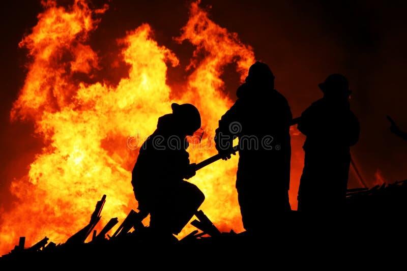 Lutadores de incêndio e flamas alaranjadas imagens de stock
