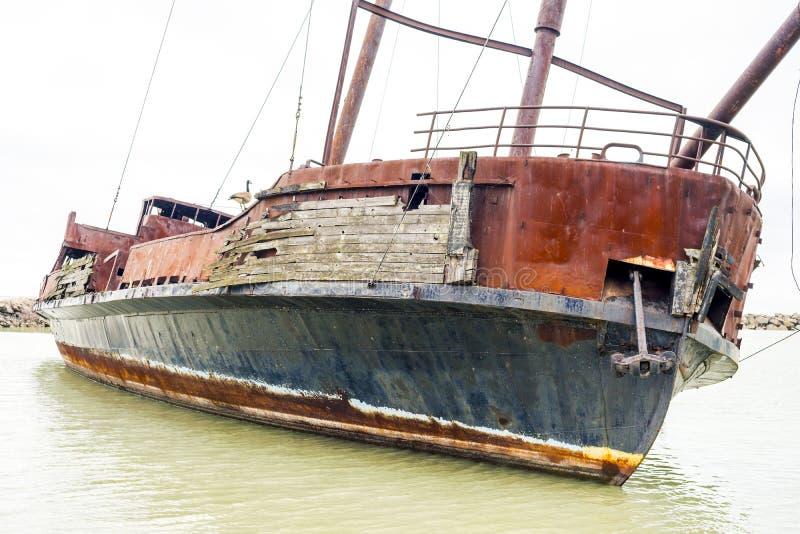 Lutande bruten och rostig skeppsbrott marooned i near kust för liten vik, royaltyfri bild