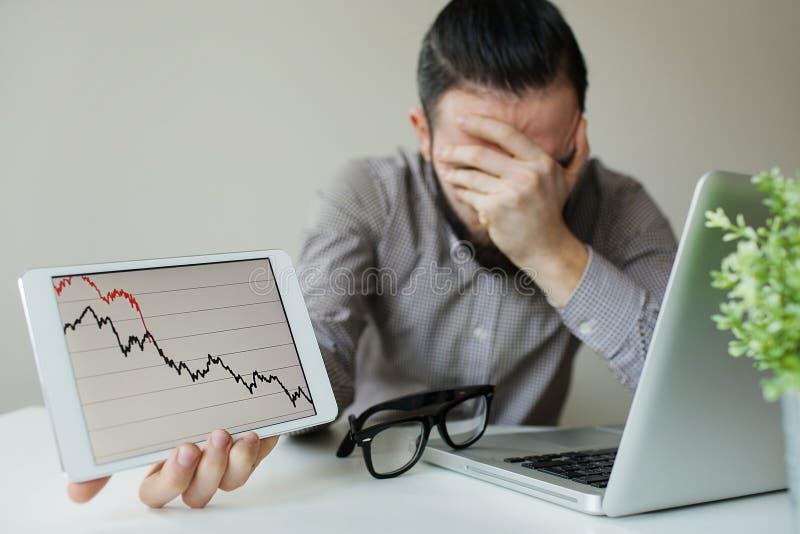 Lutande huvud för deprimerad affärsman nedanför dåligt aktiemarknaddiagram royaltyfri foto
