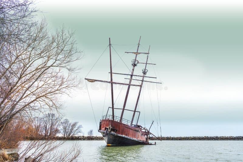 Lutande rostig skeppsbrott med högväxta master marooned i räkning nära s royaltyfri fotografi