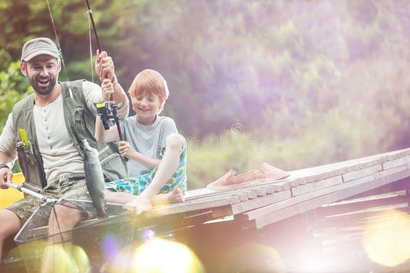 Lutandeskott av den lyckliga fadern och sonen som fångar fisken royaltyfri fotografi