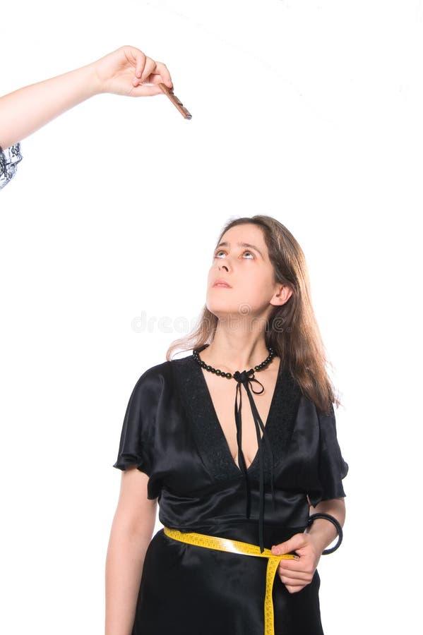 Lutas da mulher nova de encontro à tentação do chocolate fotografia de stock