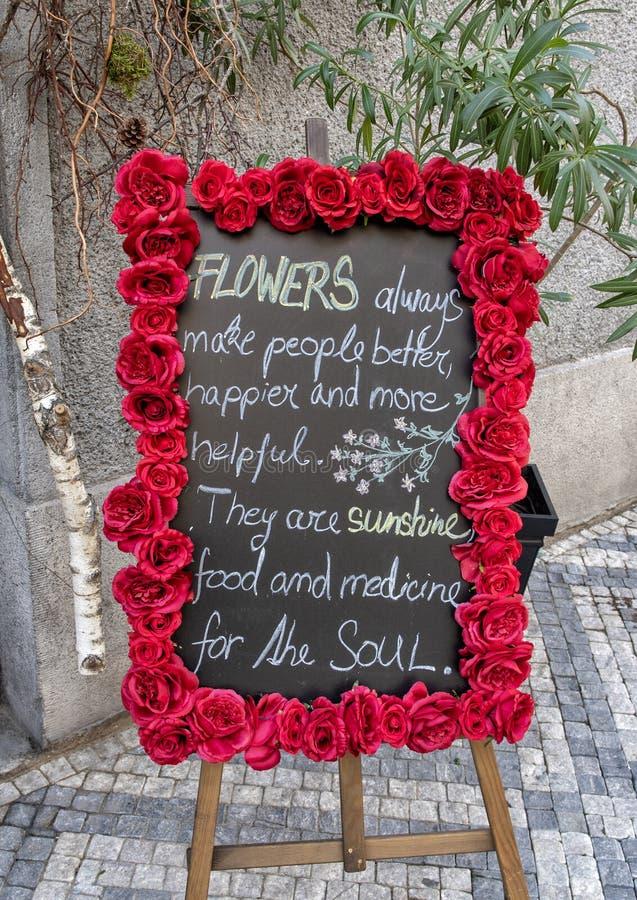Luther Burbanks sobre las flores escritas en un tablero de tiza rodeado por las rosas rojas en Praga, República Checa imagen de archivo libre de regalías