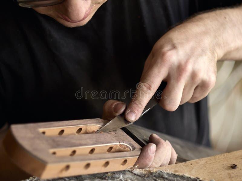 Luthier altera a cabeça da guitarra clássica imagens de stock royalty free