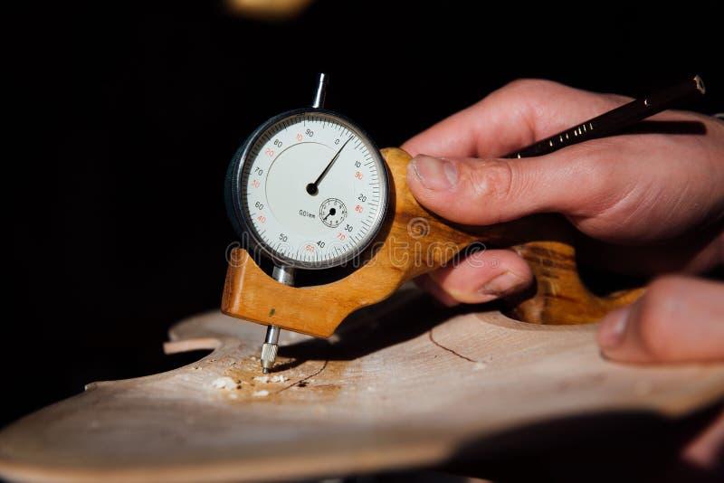 Luthier Arbeiten des Vorlagenhandwerkers an der Schaffung einer Violine sorgfältige Einzelheit über Holz stockfotos