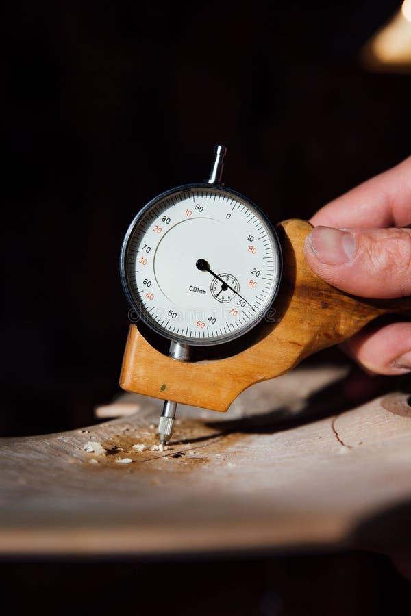 Luthier Arbeiten des Vorlagenhandwerkers an der Schaffung einer Violine sorgfältige Einzelheit über Holz lizenzfreies stockfoto