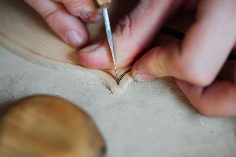 Luthier Arbeiten des Vorlagenhandwerkers an der Schaffung einer Violine sorgfältige Einzelheit über Holz lizenzfreie stockfotos