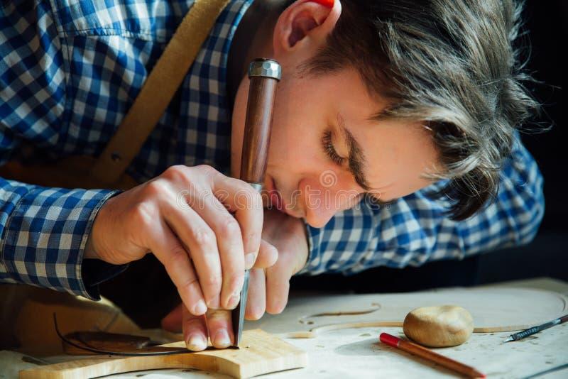 Luthier Arbeiten des Vorlagenhandwerkers an der Schaffung einer Violine sorgfältige Einzelheit über Holz stockfotografie