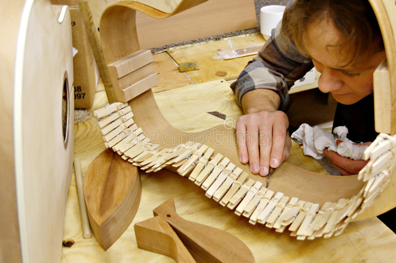Luthier Building Guitar in Workshop. A young man who is a luthier is making hand made guitar out of wood in his home workshop stock image