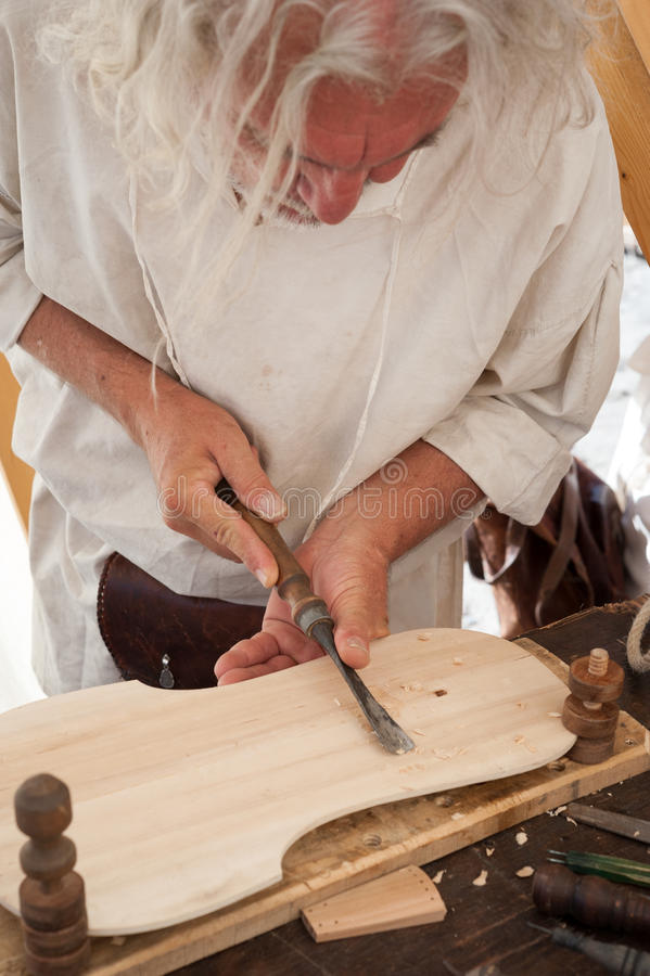 The luthier builds a medieval stringed instrument. Luthier working on the creation of a stringed instrument. He uses a chisel to carve the top royalty free stock image