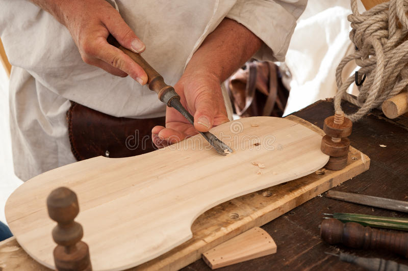 The luthier builds a medieval stringed instrument. Luthier working on the creation of a stringed instrument. He uses a chisel to carve the top stock photo