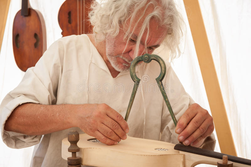 The luthier builds a medieval stringed instrument. Luthier working on the creation of a stringed instrument. He uses a large compass to take the exact measure stock photos