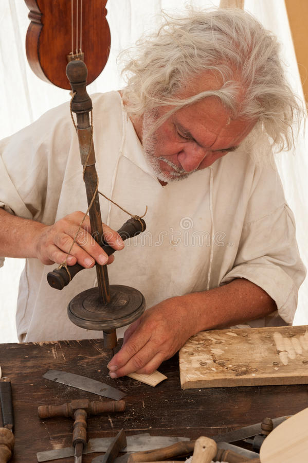 The luthier builds a medieval stringed instrument. Luthier working on the creation of a stringed instrument. He uses an old manual drill royalty free stock photo