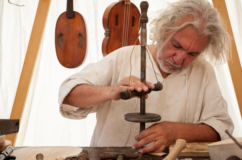 The luthier builds a medieval stringed instrument. Luthier working on the creation of a stringed instrument. He uses an old manual drill royalty free stock images