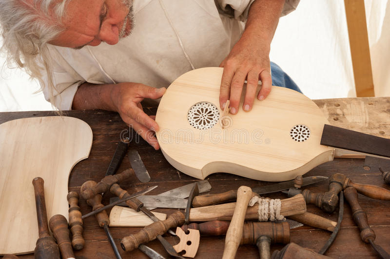 The luthier builds a medieval stringed instrument. Luthier working on the creation of a stringed instrument. Various tools and instrument are placed on the stock image