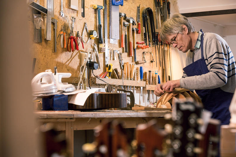 Luthier carving the body of a lute. Luthier presicely carving the body of his halfway finished lute with guitar headstocks in the foreground stock photography