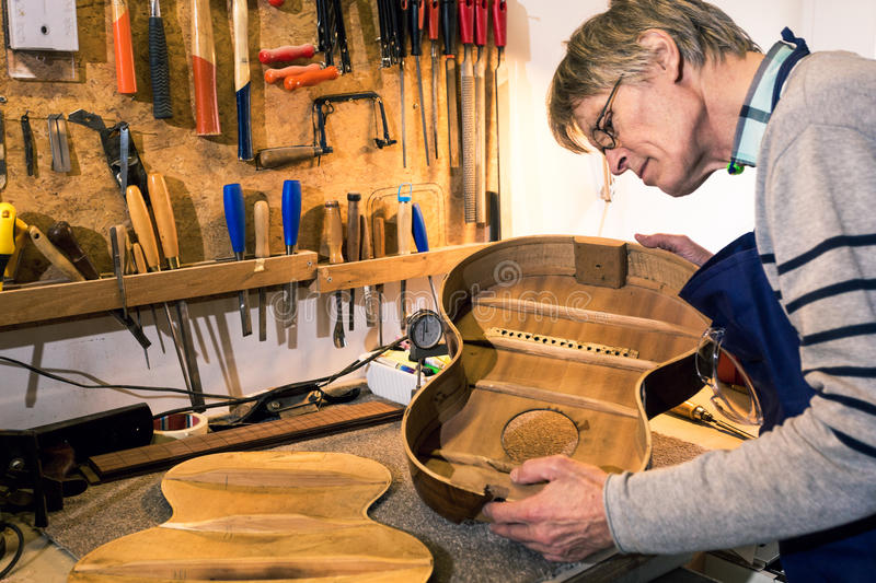 Luthier checking the body of an acoustic guitar royalty free stock photography