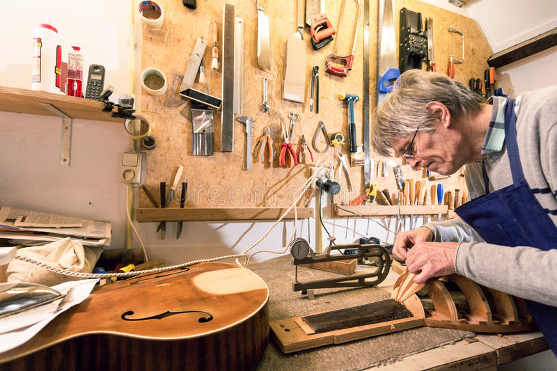 Luthier concentrating on carving a lute. In a cluttered workshop, surrounded by tools and semi finished instruments royalty free stock photo