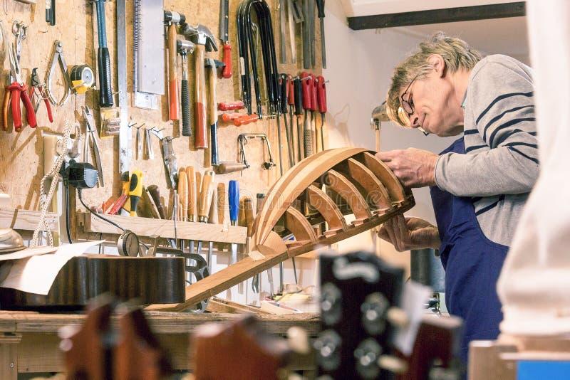Luthier die zijn halve gebeëindigde luit inspecteren royalty-vrije stock afbeeldingen