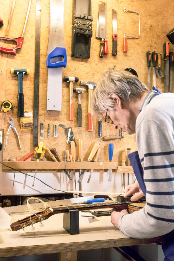 Luthier filing the frets of an acoustic guitar. To make them even royalty free stock images