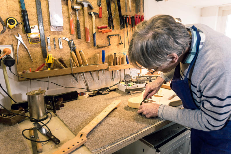 Luthier filing the neckpocket of an electric guitar. Luthier carefully filing and shaping the neckpocket of an electric guitar royalty free stock images