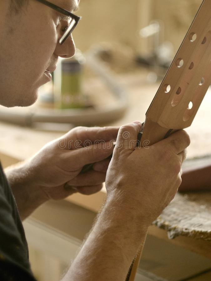 Free Luthier Is Working On The Neck Of Classical Guitar. Stock Photography - 145327422