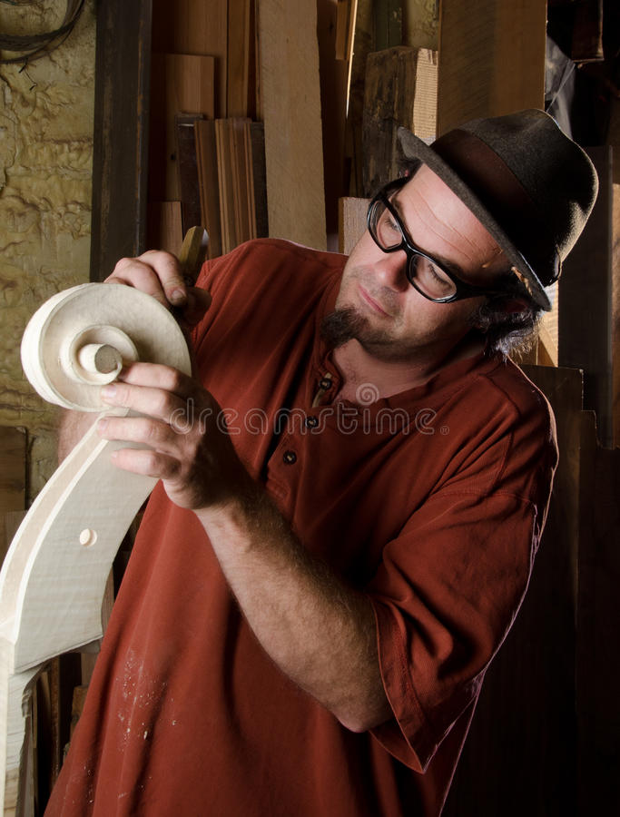 Luthier making a bass. A new-generation luthier (string instrument maker) fashions the scroll of a bass in his workshop royalty free stock photo