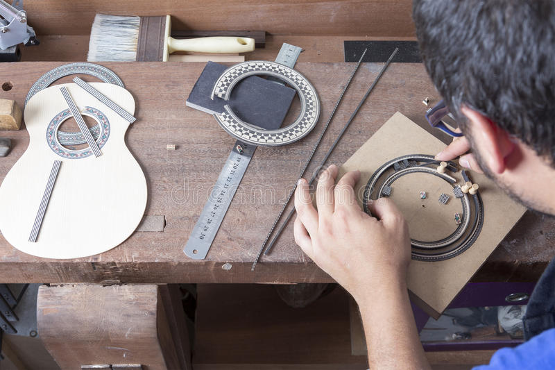 Luthier and the rosette. Luthier making a guitar rosette over a desk with the cover of the guitar beside him at the workshop royalty free stock photos