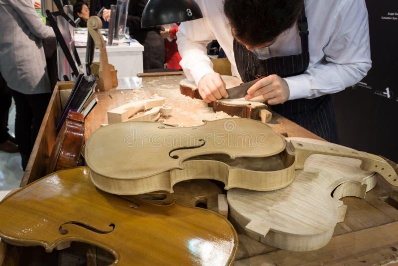 Luthier som arbetar på en fiol på biten 2014, internationellt turismutbyte i Milan, Italien fotografering för bildbyråer