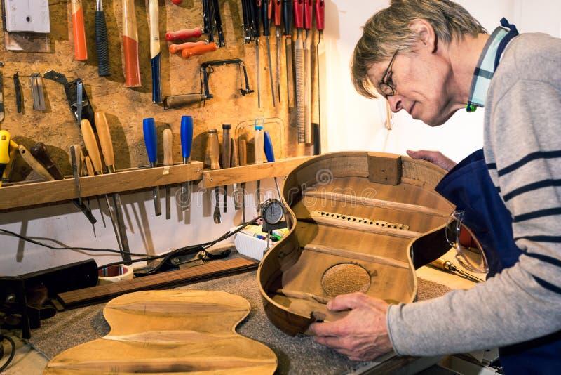 Luthier som kontrollerar kroppen av en akustisk gitarr royaltyfri fotografi