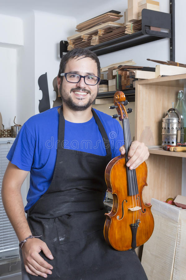 Luthier with a violin. Portrait of a young luthier with a handcrafted violin sitting at his workshop with the tools and the woods on the background royalty free stock photo