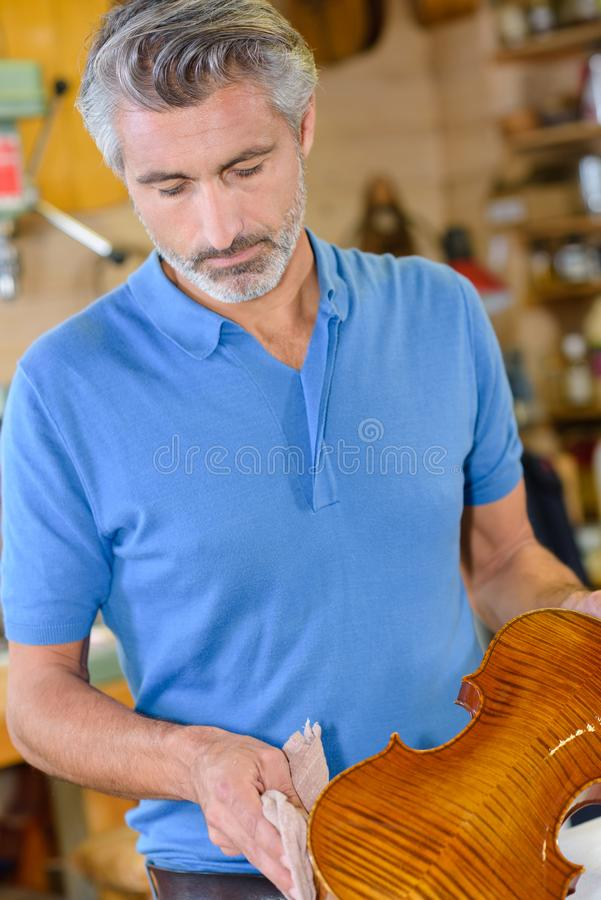 Luthier wiping a violin. Violin stock image