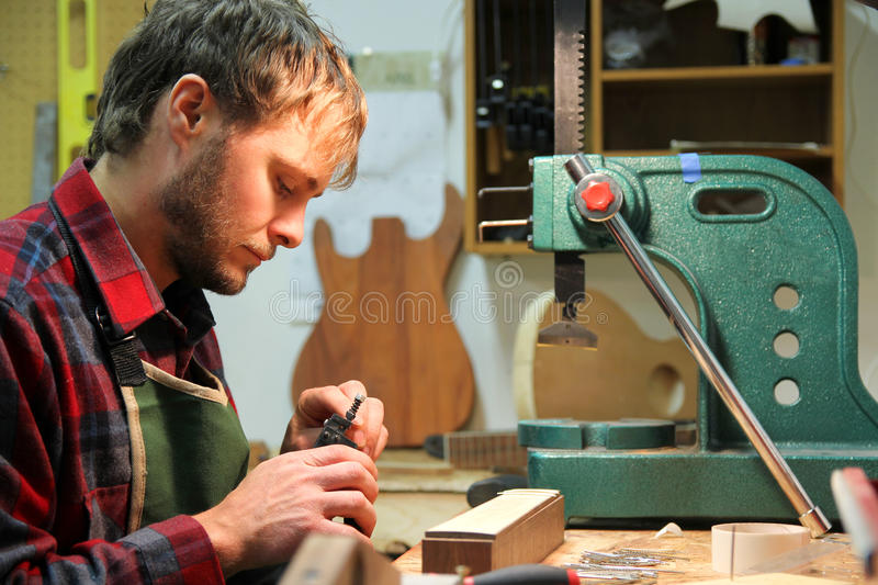 Luthier Woodworker Building Guitar in Workshop. A young man in a flannel shirt is working as a luthier, using tools to building a guitar in his home workshop stock photos