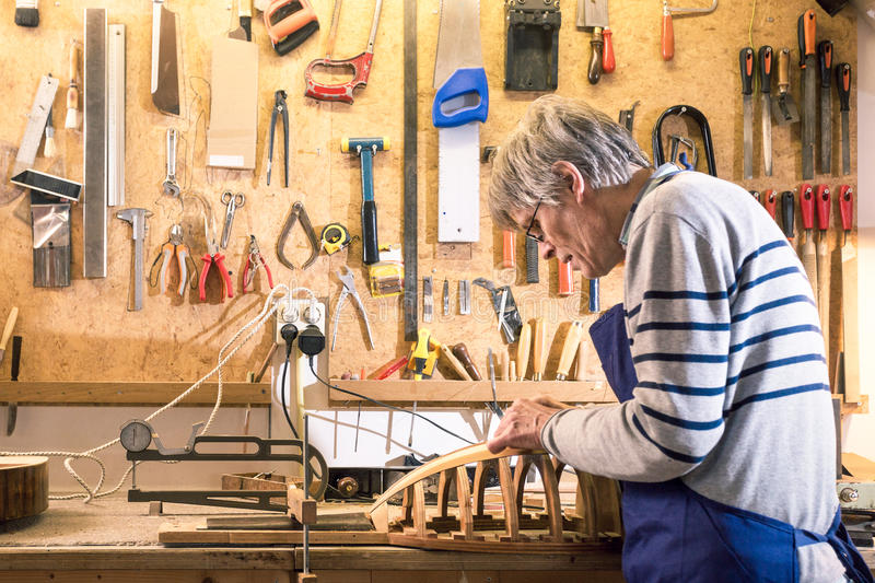 Luthier working at his lute on the workbench. With his tools on the background stock image