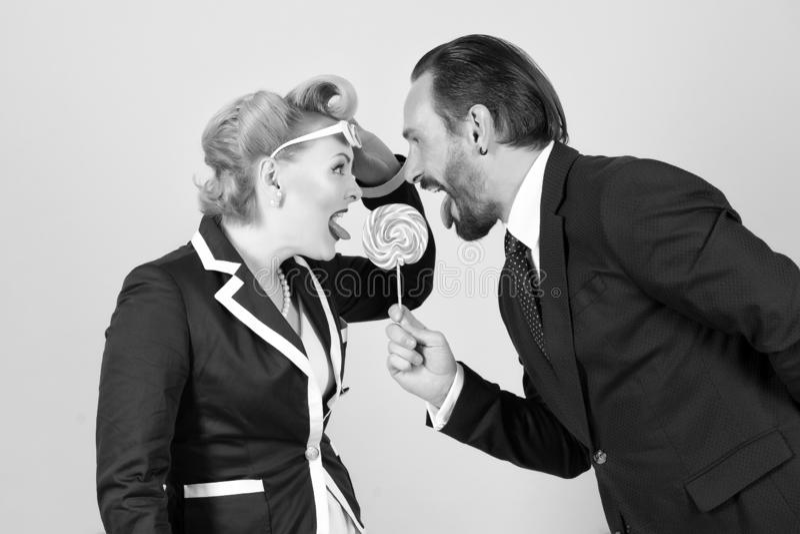 Lutscher in der Gefahr zwei Manager, die für eine Süßigkeit auf grauem Hintergrund kämpfen lizenzfreies stockbild