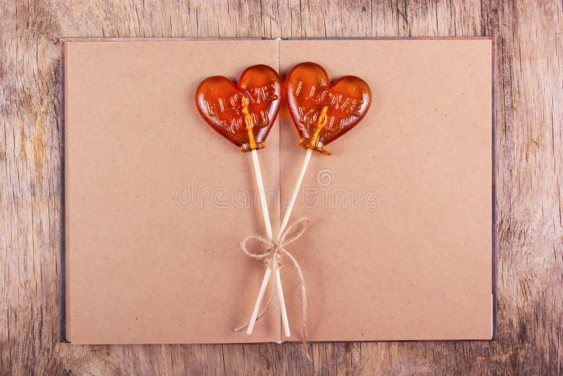 Lutscher zwei in Form eines Herzens und ein altes Tagebuch mit Leerseiten stockbild