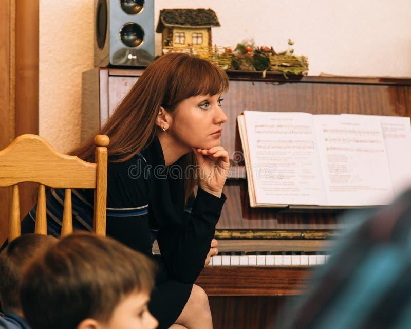 LUTSK, UKRAINE - 2. November 2017: Frau, die nahe Klavier im Kindergarten sitzt stockbilder
