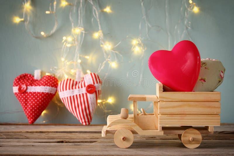 Luty 14th rocznika drewniany kalendarz z drewnianą zabawki ciężarówką z sercami przed chalkboard zdjęcie stock