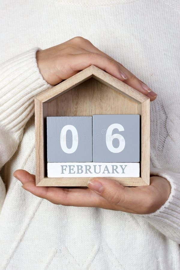 Luty 06 w kalendarzu dziewczyna trzyma drewnianego kalendarz barmanu dzień zawody międzynarodowe s zdjęcie stock